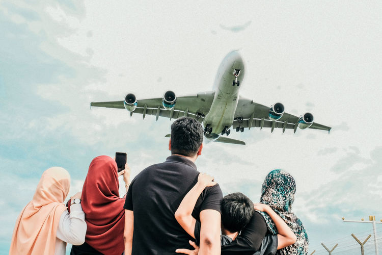 Rear View Of Family Looking At Airplane Flying Against Sky