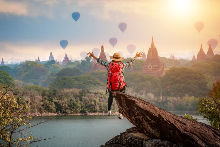Woman traveler sitting on stone freedom hands up watching and enjoying with Bagan pagoda landscape in Mandalay Myanmar. Real People One Person Water Rear View Beauty In Nature Sky Nature Balloon Leisure Activity Lifestyles Mountain Scenics - Nature Architecture Men Full Length Built Structure Plant Casual Clothing Outdoors Human Arm Myanmar Bagan Travel Destinations Mandala Burma The Traveler - 2019 EyeEm Awards