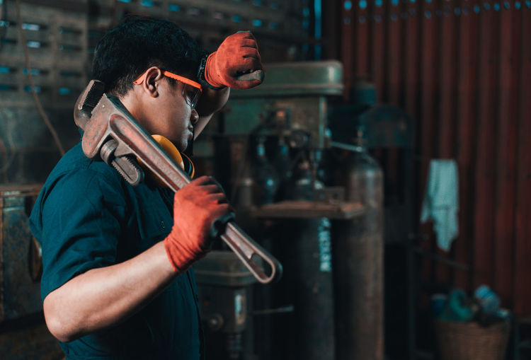 Man holding equipment while working in factory