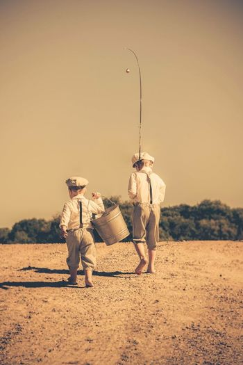 Rear view of siblings with bucket and fishing rod walking on field against sky