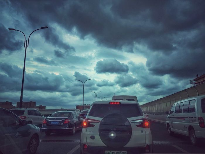 Cars on road in city against cloudy sky