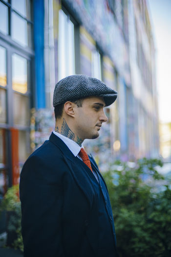 Thoughtful businessman looking away while standing outside building