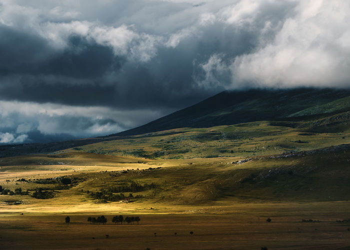 Valley illuminated by the sun through storm clouds.