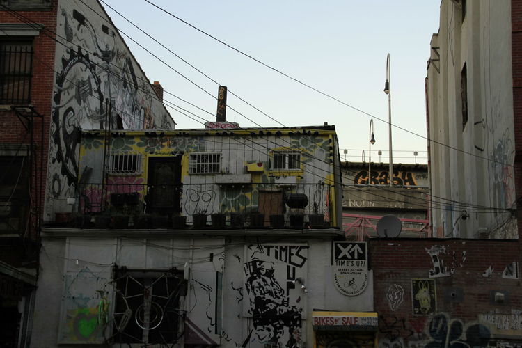 Graffiti on building against sky in city