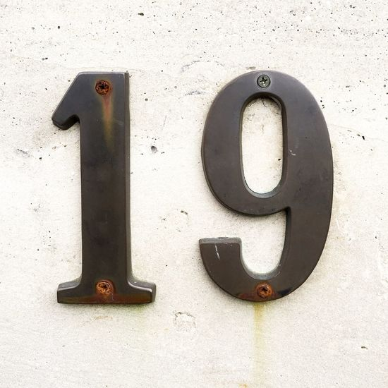 Number 19 on old stone wall 19 Nineteen Number Numbers Weathered Screws Screwed Fixed Address Numerals Stone Wall Text Sign Old Metal Metallic