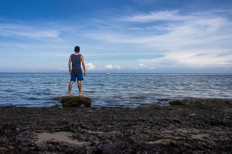 Rear View Of Man Standing On Rock At Seashore Against Sky