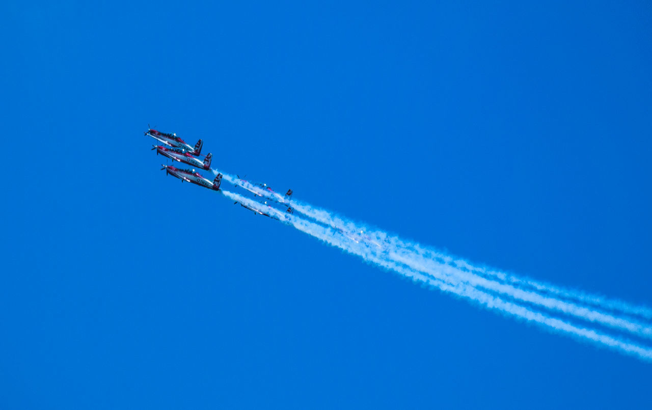 airplane, transportation, vapor trail, blue, flying, airshow, air vehicle, mode of transport, low angle view, speed, smoke - physical structure, travel, clear sky, mid-air, day, fighter plane, military airplane, sky, aerobatics, outdoors, no people, stunt, teamwork, aerospace industry, nature