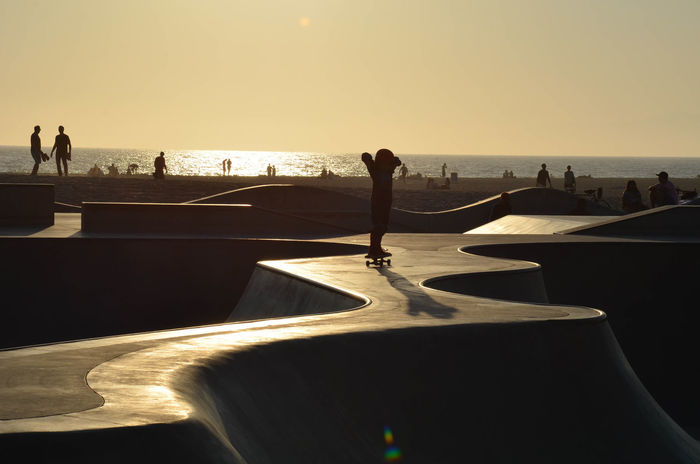 Starting out early Children Kids Skateboarding Skatepark Skill  Working Beach Horizon Over Water Improving Leisure Activity Lifestyles Nature Playing Practicing Real People Scenics Sea Silhouette Skateboard Park Sport Sunlight Sunset Train Vacations Weekend Activities
