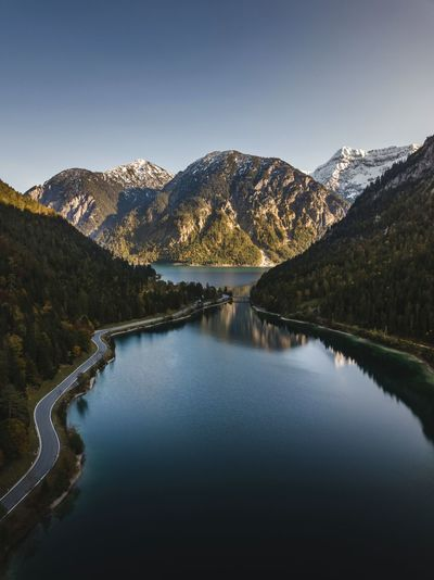 Scenic view of lake and mountains against clear sky drone