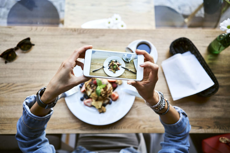 Midsection of woman photographing with mobile phone on table