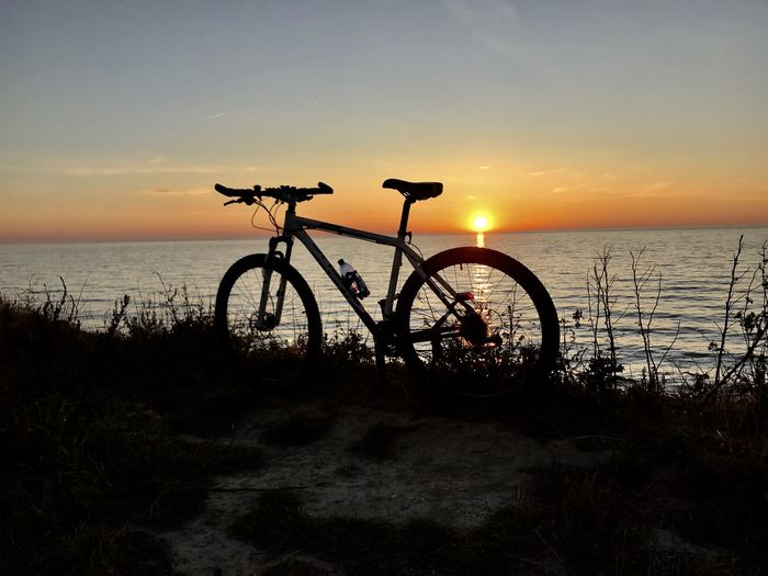 Bicycle by sea against sunset sky
