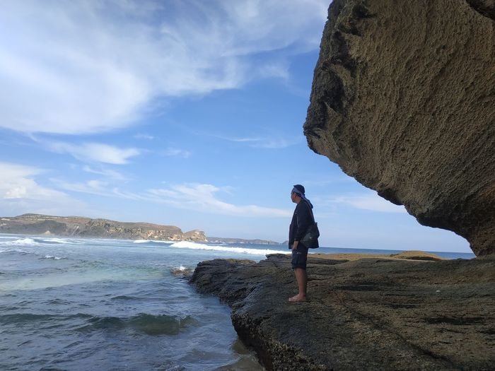 Man standing on rock at beach against sky