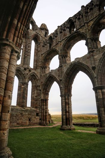 Whitby Whitby Whitby Abbey History Arch Architecture The Past Built Structure Sky Ancient Grass Nature Day Old Ruin No People Tourism Travel Destinations Travel Clear Sky Low Angle View Ruined Outdoors Old Ancient Civilization Archaeology Architectural Column Abbey