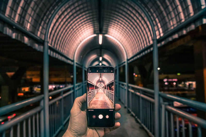 Man hand holding a mobile phone capturing a bridge Architecture Human Body Part Illuminated Built Structure Human Hand Hand Holding Real People Connection Transportation Lifestyles Railing Focus On Foreground Mode Of Transportation Bridge Unrecognizable Person Transparent Mobile Phone LINE Convergence Bangkok Capture