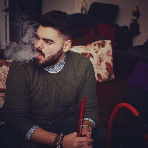 Young man smoking hookah while sitting at home