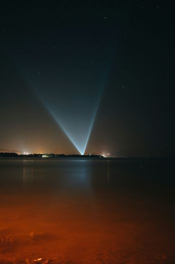 Distant view of illuminated laser light by lake against sky at night