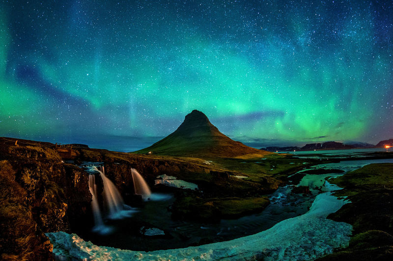 Scenic View Of Mountain And Waterfall Against Sky At Night