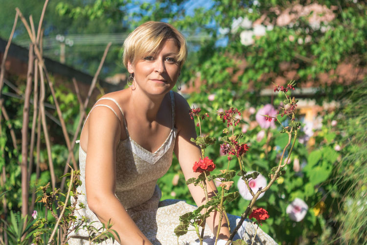 Portrait of beautiful woman against white flowering plants