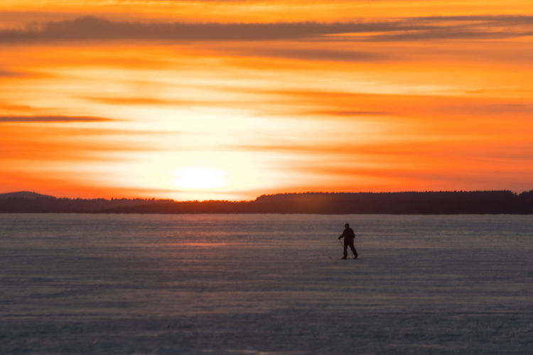 Sky Ski Skiing Scenics - Nature Beauty In Nature Tranquility Tranquil Scene Nature Canada Coast To Coast Orange Color Orange Orange Sky Sunset Silhouette One Person Water Real People Land Full Length Lifestyles Cloud - Sky Sea Unrecognizable Person Leisure Activity Outdoors