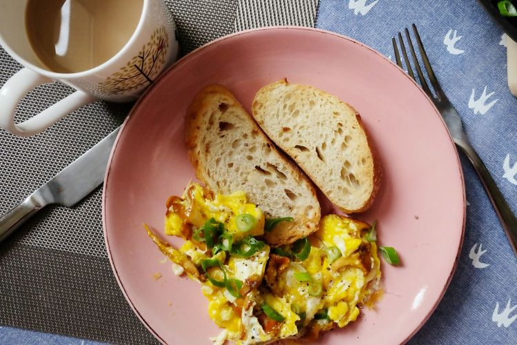 High Angle View Of Scrambled Eggs And Bread In Plate On Table