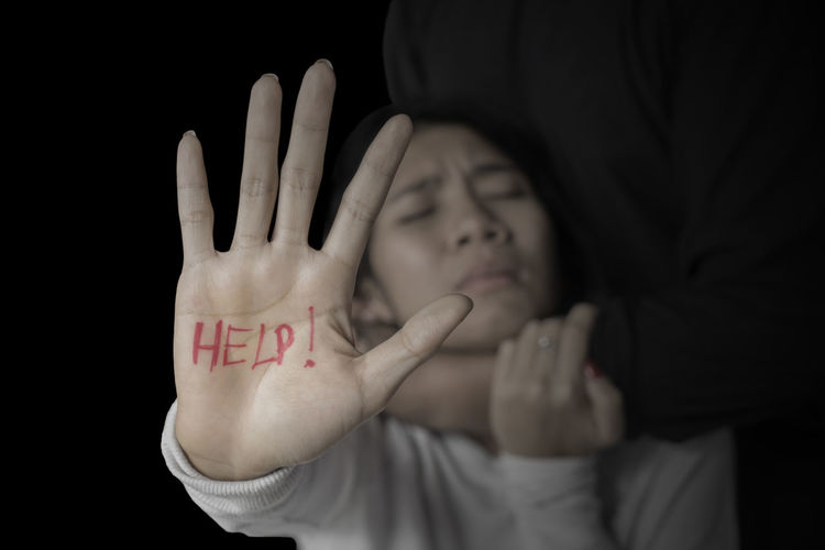 Black Background Body Part Communication Finger Front View Gesturing Hand Headshot Human Arm Human Body Part Human Hand Indoors  Obscured Face One Person Palm Portrait Showing Stop Gesture Text Western Script Women Young Adult