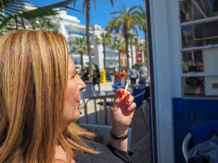 Close-up of woman smoking cigarette while sitting at sidewalk cafe