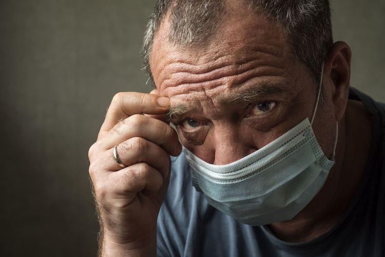 Tired male doctor in medical mask