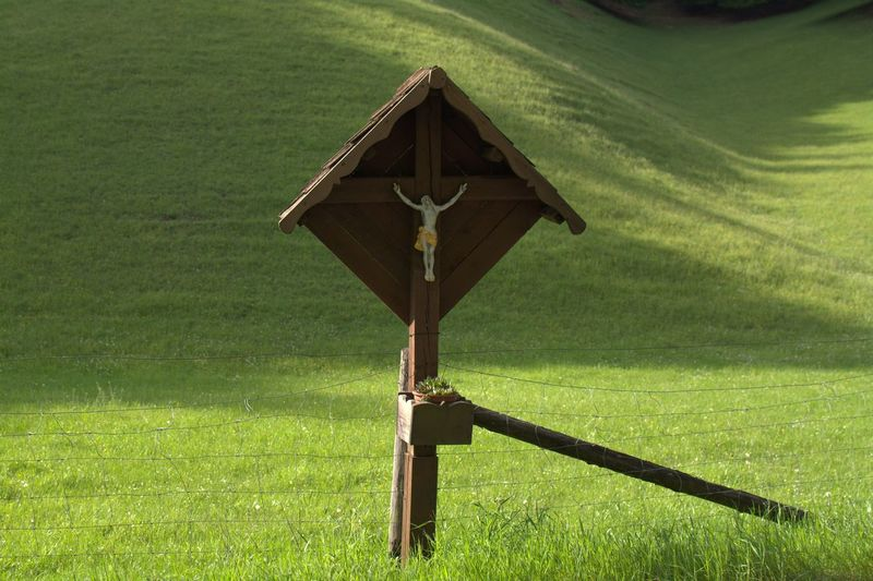 Jesus figurine on wooden pole at grassy field