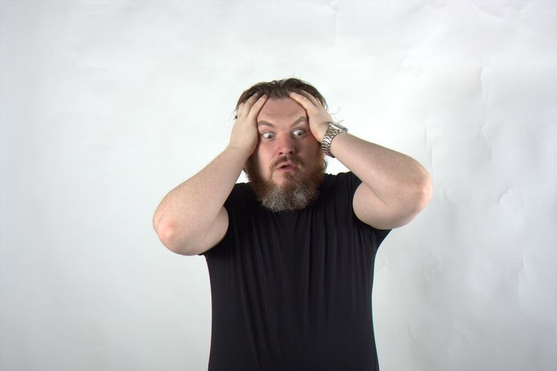 Frustrated Man Standing Against White Background