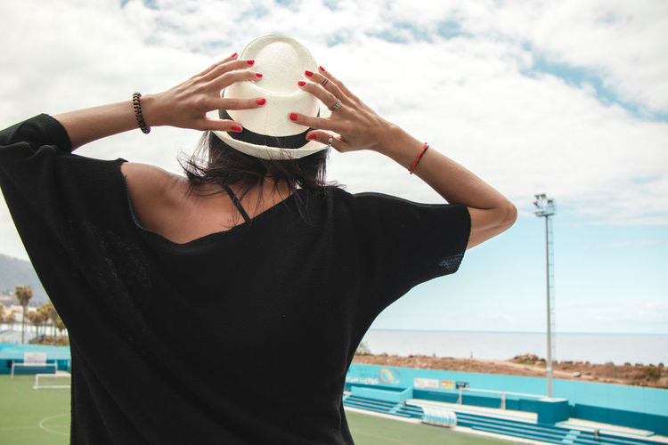 Midsection of woman wearing hat against sky