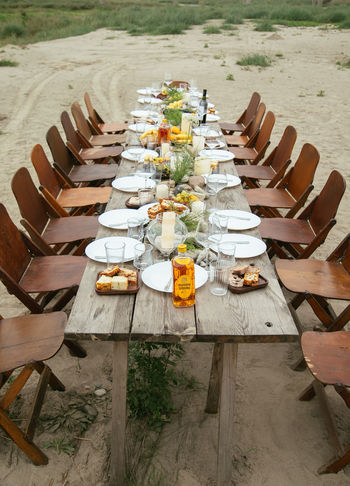 Arrangement Celebration Chair Crockery Food Food And Drink Freshness Glass High Angle View In A Row Land Large Group Of Objects Nature No People Order Outdoors Place Setting Plant Plate Seat Setting Table Wood - Material
