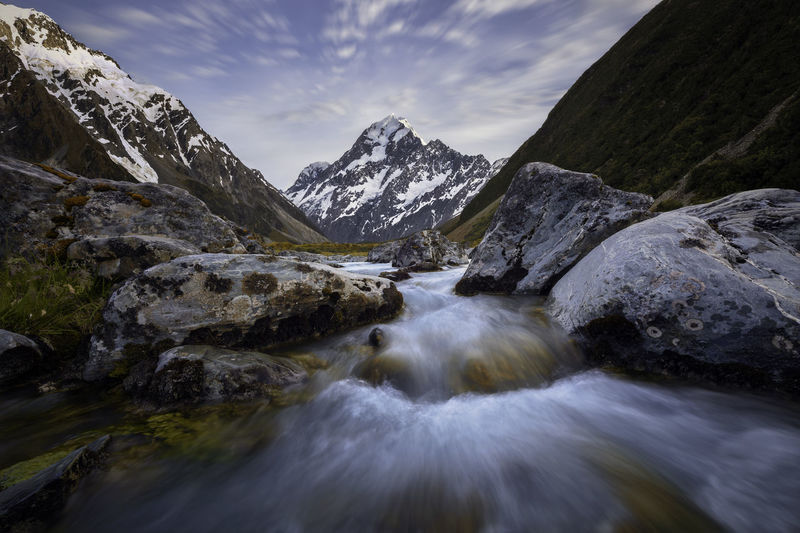 Dramatic sky over river Mount Cook in New Zealand Mountain Peak Rocky Mountains Rock Beauty In Nature Motion Scenics - Nature Water Blurred Motion No People Long Exposure Sky Nature Solid Rock - Object Flowing Water Mountain Tranquil Scene Cloud - Sky Non-urban Scene Idyllic Tranquility Outdoors Flowing Stream - Flowing Water Snowcapped Mountain