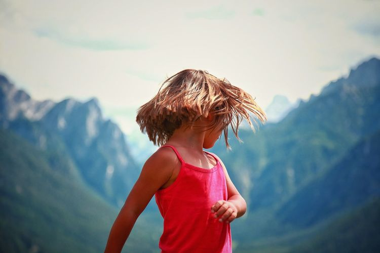 Blond girl tossing hair against mountains