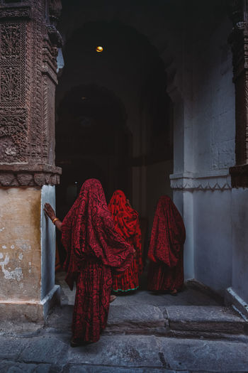 Rear view of women standing in red traditional clothing at temple