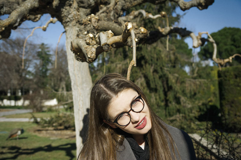 Portrait of young woman wearing eyeglasses standing against trees in park