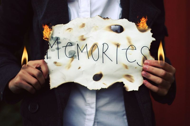 Mid Section View Of Man Holding Burning Paper With Text Memories On It