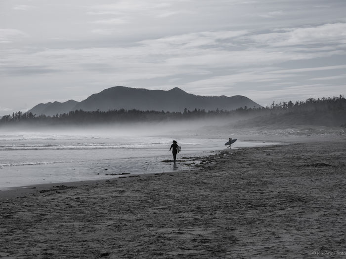 Surfers with surfboard walking on shore at beach against cloudy sky