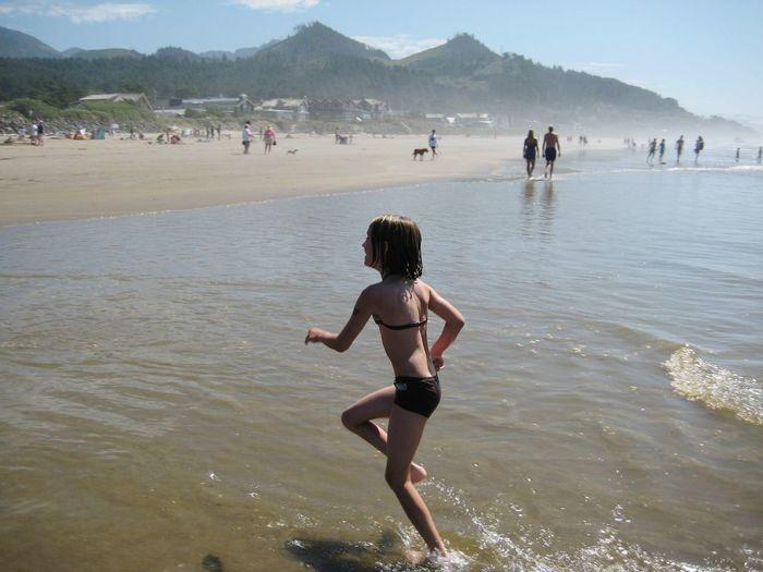 Happy bikini girl running at beach