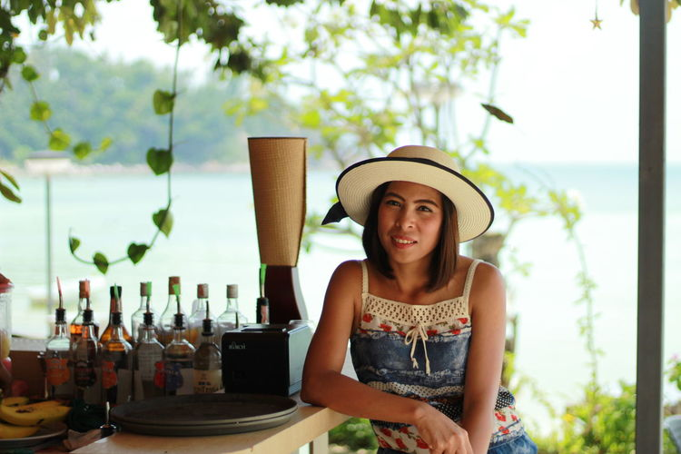 Portrait of woman sitting at bar counter against sea