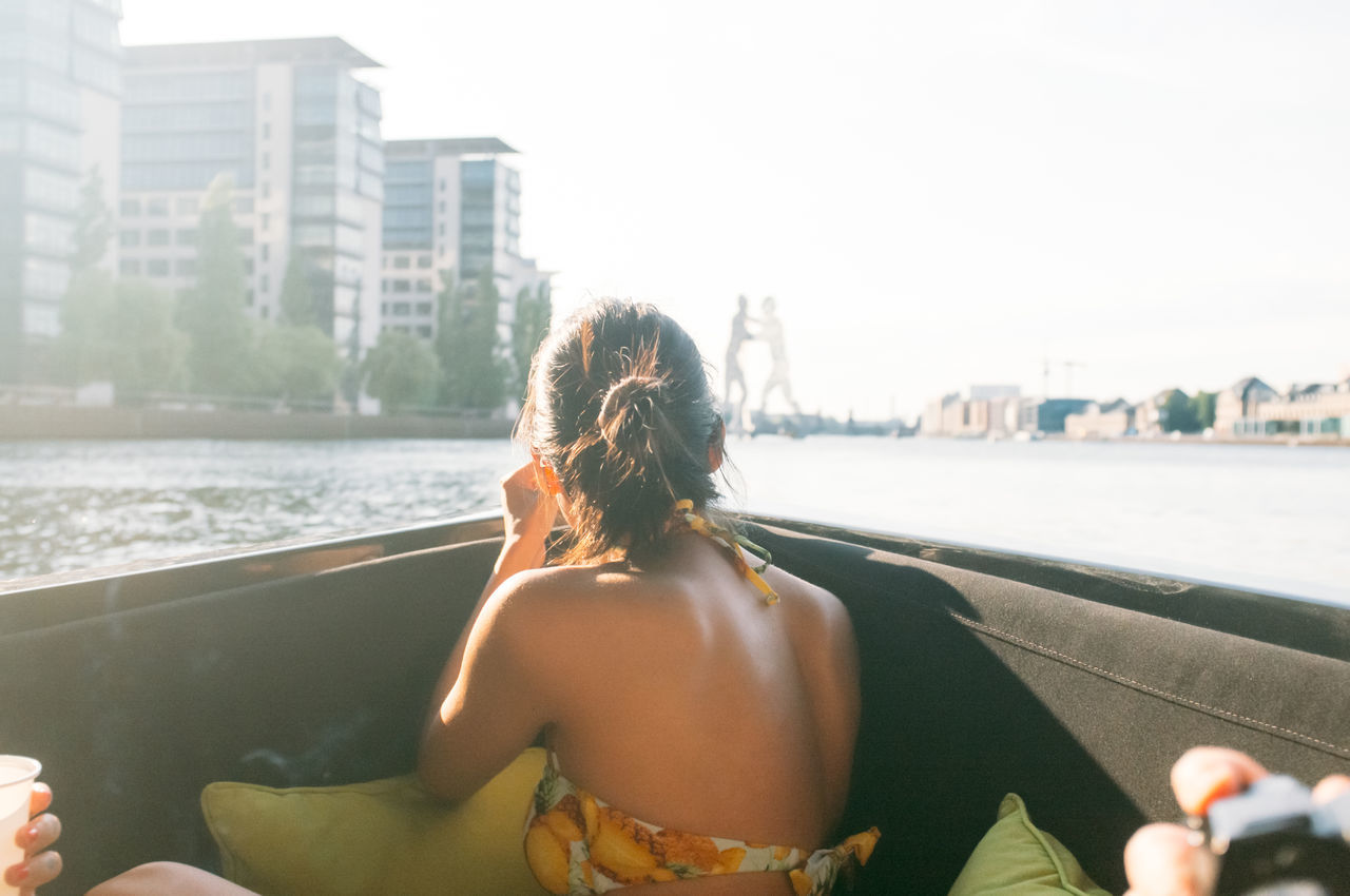 Rear view of woman sitting and enjoying in boat at river