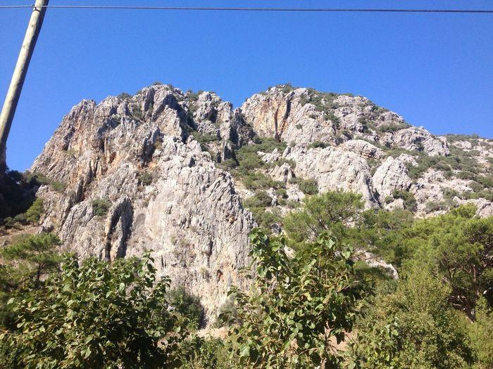 """""""Olympos"""" kelimesinin eski Yunanca 'da """"ulu dağ"""" anlamına geldiğine inanılmaktadır. Dünya üzerinde yirmiden fazla dağ ve tepe bu adı taşımaktadır ve bazılarının yakınlarındaki kasaba ve şehirler de bu adı almıştır. Bu tepelerin en ünlüsü, Yunanistan'ın kuzey doğusunda bulunan, eski Yunan tanrılarının evi sayılan, Thessalian tepesidir. Olympos Antik Şehri adını, eskiden Olympos Dağı olarak bilinen Tahtalı dağından alır. Natural Nature Olimpos, Kemer Turkey Türkiye Doğa Kemer Antalya Kumluca Olimpos Olympos Antalya"""