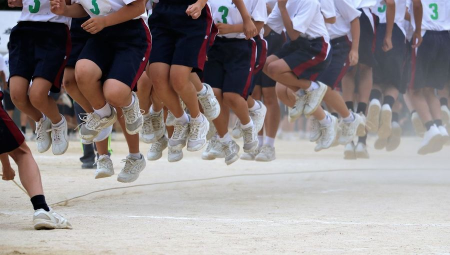 Low section of people jumping over a skipping rope