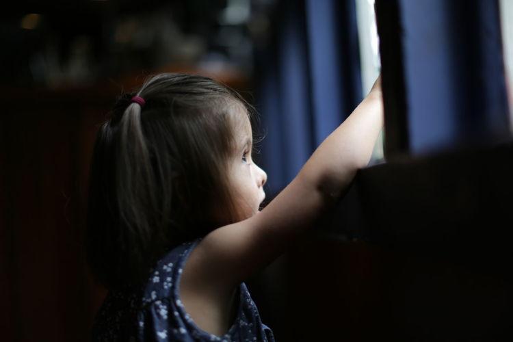 Thoughtful girl looking through window