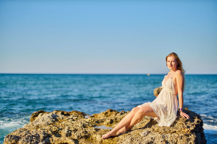 Portrait Of Beautiful Woman Sitting On Rock Against Sea At Beach
