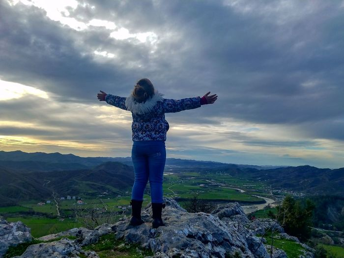 Rear View Of Girl With Arms Outstretched Standing On Cliff Against Cloudy Sky