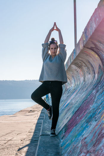 Full length of young woman doing yoga by wall against clear sky