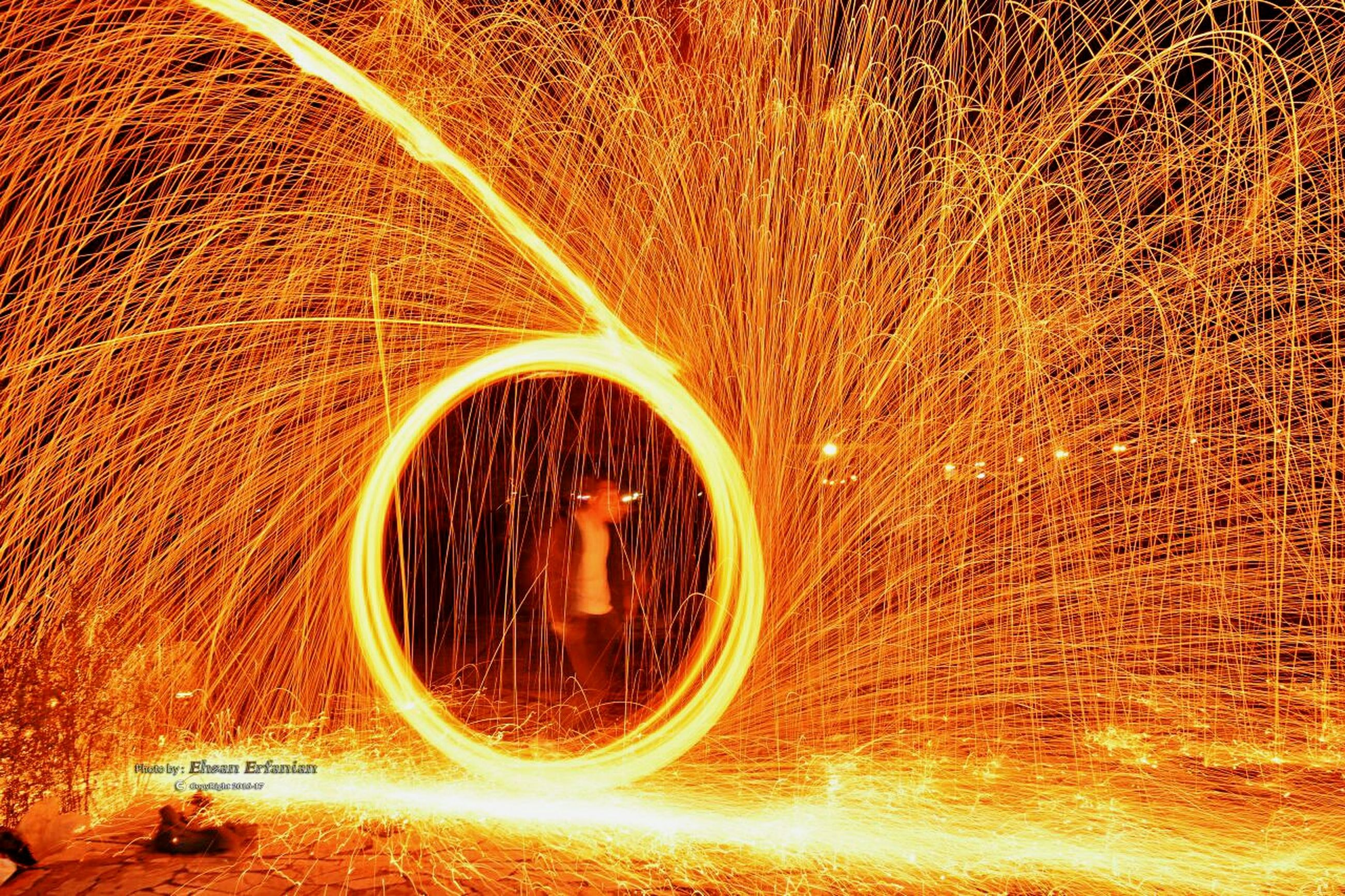 circle, close-up, motion, illuminated, orange color, abstract, long exposure, light painting, no people, blurred motion, multi colored, burning, glowing, outdoors, yellow, pattern, bicycle, part of, night, light trail