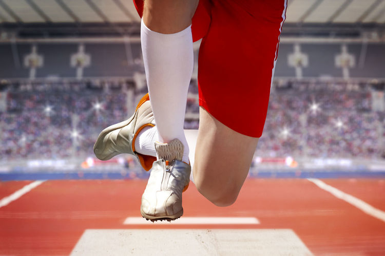 Low section of sportsperson jumping at stadium