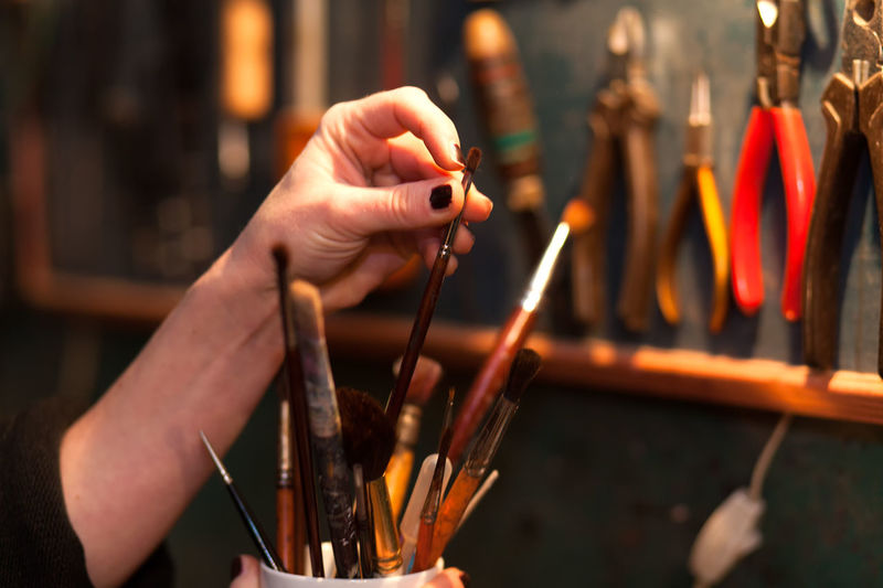 Close-up of hand holding paint brushes at workshop