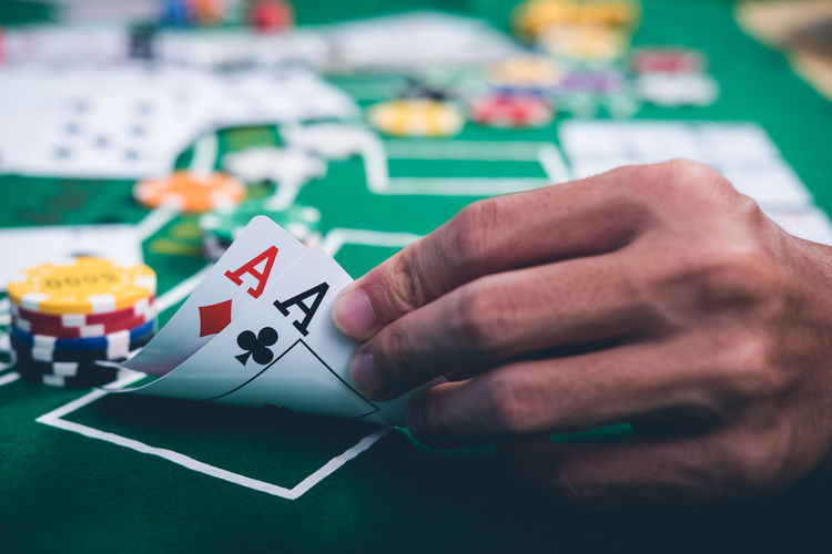 Gambling chips and cards on a green cloth Casino table Close-up Day Gambling Gambling Chip Holding Human Body Part Human Hand Indoors  Leisure Activity Leisure Games Men One Person People Playing Real People Table